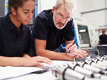 stock-photo-opprentice-planning-cnc-machinery-project
